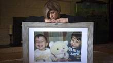 Tima Kurdi sits for a photograph in August, 2016, with a picture of her late nephews, Alan, left, and Ghalib at her home in Coquitlam, B.C. 'Something must be done,' Ms. Kurdi says of their deaths. (DARRYL DYCK/THE CANADIAN PRESS)