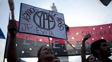Demonstrators in Buenos Aires on Monday hold up a banner that reads in Spanish 'We are going for all YPF,' in support of a bill proposed by Argentina's President Cristina Fernandez to expropriate 51 per cent of the shares of YPF oil company that is controlled by Spain's Repsol. (Natacha Pisarenko/Natacha Pisarenko/Associated Press)