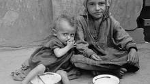 This 1941 photo provided by the United States Holocaust Memorial Museum, shows two destitute children sitting with empty bowls on a street in the Warsaw ghetto. (Willy Georg/AP Photo/United States Holocaust Memorial Museum, Willy Georg)