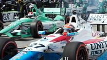 James Hinchcliffe races out of the pits in front of Charlie Kimball (83) in the first Toronto Indy race of the day in Toronto on Sunday, July 20, 2014. (Frank Gunn/THE CANADIAN PRESS)