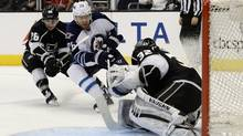 Winnipeg Jets right wing Blake Wheeler (26) scores a goal against Los Angeles Kings goalie Jonathan Quick (32) as Kings' Slava Voynov (26) defends during the third period of an NHL hockey game Saturday, March 29, 2014, in Los Angeles (Associated Press)