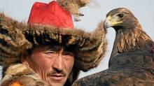 A Kazakh eagle hunter surveys the field, near Olgi, Western Mongolia. (Janine Murphy)