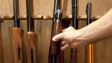 A rifle owner opens his gun cabinet. (Sean Kilpatrick/THE CANADIAN PRESS)