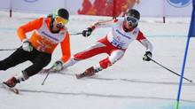 Mac Marcoux of Canada, right, and his guide Robin Femy race to win 3rd place in the men's downhill, visually impaired event. (Dmitry Lovetsky/AP)