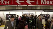 Commuters exit a subway onto the TTC subway platform at Bloor-Yonge station in Toronto. (PETER POWER/THE GLOBE AND MAIL)