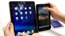 People compare the performance of Apple's iPad and Samsung's Galaxy Tab tablet. (Thomas Peter/Reuters)