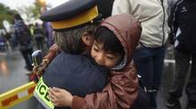 Staff Sergeant Denise Vautour receives a hug from 6 year old Tobe Tong after a vigil outside the Codiac RCMP Detachment in Moncton, New Brunswick on June 6 2014. (Fred Lum/The Globe and Mail)