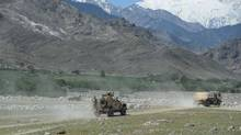U.S. armoured vehicles patrol near the site of a U.S. bombing during an operation against Islamic State militants in the Achin district of Nangarhar province, Afghanistan, on April 15, 2017. (NOORULLAH SHIRZADA/AFP/Getty Images)