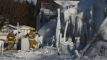 Firefighters work at the scene of a fire at a retirement home in L'Isle-Verte, Que., on Jan. 23, 2014: 32 people are dead or missing. (Christinne Muschi For The Globe and Mail)