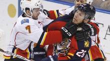 Florida Panthers Mikael Samuelsson (C), is roughed up by Calgary Flames T.J. Brodie (L), and Olli Jokinen during second period of NHL game in Sunrise, Florida December 16, 2011. (HANS DERYK/REUTERS)