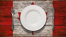 A plate and cutlery sit on a wooden table stencilled with the Canadian flag. (iStockphoto)