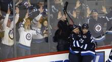 Winnipeg Jets' Bryan Little (18) and Zach Redmond (25) celebrate after the pair combined for Little's game winning goal against the Florida Panthers during NHL action overtime action in Winnipeg, Tuesday, February 5, 2013. (Trevor Hagan/THE CANADIAN PRESS)