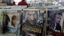 Pirated CDs and DVDs at a Beijing store last April. Trade officials and industry executives have cautioned against too high expectations of Beijing's latest move to combat counterfeit goods. (JASON LEE/JASON LEE/REUTERS)