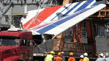 FILE - In this Sunday, June 14, 2009 file photo shows workers unloading debris, belonging to crashed Air France flight AF447, from the Brazilian Navy's Constitution Frigate in the port of Recife, northeast of Brazil. (Eraldo Peres/AP)