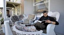 Author and cartoonist Kevin Sylvester reads on the front porch of his Toronto home. (Fred Lum/ The Globe and Mail)