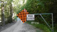B.C. Transportation Ministry pictures indicate the driver of a tanker truck containing 35,000 litres of jet fuel drove around a metal barricade warning of a road closure before the rig tumbled into a creek in B.C.'s West Kootenay region. (The Canadian Press)