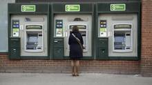 A customer using an outdoor TD Canada Trust Green Machine atm at the corner of Church and Wellesley in Toronto. (Fred Lum/The Globe and Mail)