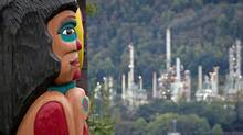 A totem pole on the Tsleil-Waututh First Nation that was a gift from the Lummi Nation in Washington state, frames the Chevron Burnaby Oil Refinery in the distance after the totem was unveiled during a ceremony in North Vancouver, B.C., on Sunday September 29, 2013. The totem pole is meant to be a symbol of cross-border unity among Coast Salish nations opposing the proposed Kinder Morgan pipeline expansion and expanded oil tanker traffic. THE CANADIAN PRESS/Darryl Dyck (Darryl Dyck/CP)