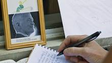 A woman signs a book of condolences outside late NDP leader Jack Layton's constituency office in Toronto on Aug. 23, 2011. (Aaron Vincent Elkaim/THE CANADIAN PRESS)