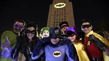 Fans dressed as characters from Batman pose in front of a Bat-Signal projected onto City Hall as a tribute to Adam West on June 15, 2017, in Los Angeles. (Chris Pizzello/Chris Pizzello/Invision/AP)