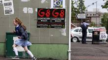 A girl runs past anti-G8 posters in West Belfast on June 14, 2013. Leaders of the G8 countries will meet at Lough Erne in Northern Ireland for the G8 Summit on June 17 and 18. (CATHAL MCNAUGHTON/Reuters)
