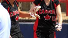 Canada's Victoria Hayward (8) and Melanie Matthews (12) celebrate after scoring against Netherlands in the second inning of the third place World Cup of Softball game in Oklahoma City, Monday, July 2, 2012. (Sue Ogrocki/AP)