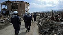 Rescue workers walk among destroyed houses and debris in the tsunami-damaged city of Rikuzen-Takata on March 24, 2011. (NICOLAS ASFOURI/NICOLAS ASFOURIAFP/Getty Images)