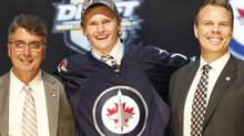 Jacob Trouba, center, stands with coach Claude Noel (left) and general manager Kevin Cheveldayoff (Keith Srakocic/The Associated Press)