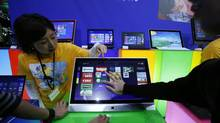 People try out Microsoft Corp.'s Windows 8 operating system at an event for its debut at the Akihabara electronics store district in Tokyo, Oct. 25, 2012. (Toru Hanai/REUTERS)