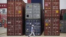 An employee walks past shipping containers at a port near Yangtze River in Wuhan, Hubei province. (DARLEY SHEN/REUTERS)