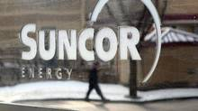 A pedestrian is reflected in a Suncor Energy sign in Calgary, Feb. 1, 2010. (Jeff McIntosh/THE CANADIAN PRESS)