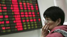 An investor looks at the stock price monitor at a private securities company Thursday, March 22, 2012, in Shanghai, China. (STR/AP)