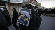 A Bahraini protester holds a picture of Saudi Shiite cleric Sheikh Nimr al-Nimr during a rally denouncing his execution by Saudi Arabia, Sunday, Jan. 3, 2016, in Daih, Bahrain. Saudi Arabia announced the execution of al-Nimr on Saturday along with 46 others. Al-Nimr was a central figure in protests by Saudi Arabia's Shiite minority until his arrest in 2012, and his execution drew condemnation from Shiites across the region. (Hasan Jamali/AP)