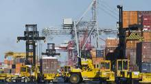 Trucks unload containers from cargo ships in the Port of Montreal in this file photo. (Graham Hughes/THE CANADIAN PRESS)