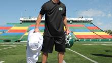 Saskatchewan Roughriders receiver Weston Dressler picks up his gear after a practice held at Mosaic Stadium in Regina on Thursday. (Michael Bell/THE CANADIAN PRESS)