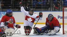 Canada's Billy Bridges celebrates a goal against the Czech Republic's Michal Vapenka during their ice sledge hockey game at the 2014 Sochi Paralympic Winter Games, March 11, 2014. (ALEXANDER DEMIANCHUK/REUTERS)
