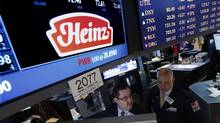 Traders work at the post that trades H.J. Heinz Co. on the floor of the New York Stock Exchange, Feb. 14, 2013. (BRENDAN MCDERMID/REUTERS)