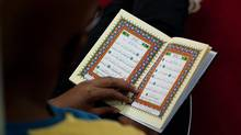 A man reads the Koran before sunrise prayer on the first day of Ramadan in August, 2011, at the Masjid mosque in downtown Toronto. (Aaron Vincent Elkaim For The Globe and Mail)