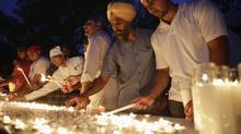 Mourners prepare for a candlelight vigil in Brookfield, Wisc., after a gunman killed six Sikh worshippers. (JOHN GRESS/REUTERS)