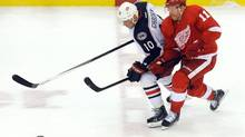 Detroit Red Wings right winger Daniel Alfredsson, right, battles for control of the puck with Columbus Blue Jackets right winger Marian Gaborik during the third period of an NHL hockey game Tuesday, Oct. 15, 2013, in Detroit. (Lon Horwedel/THE CANADIAN PRESS)