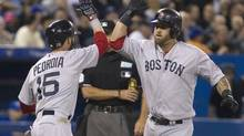 Boston Red Sox's Dustin Pedroia (L) congratulates team mate Mike Napoli at home plate after he hit a two run home run against the Toronto Blue Jays in the fifth inning of their MLB American League baseball game in Toronto April 5, 2013. (FRED THORNHILL/REUTERS)