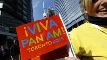 A woman holds a Viva Pan Am 2015 flag on the street during the official launch of the 2015 Pan/Parapan American Games in Toronto in Sept., 2010. (Deborah Baic/The Globe and Mail/Deborah Baic/The Globe and Mail)