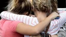Students embrace outside Burnsview Secondary School as they gather for a meeting to be updated on the death of 15-year-old Laura Szendrei, who attended the school, in Delta, B.C., on Monday September 27, 2010. (Darryl Dyck/ The Canadian Press/Darryl Dyck/ The Canadian Press)