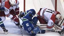 Vancouver Canucks centre Brandon Sutter tries to get a shot past Carolina Hurricanes goalie Eddie Lack as Carolina Hurricanes defenseman Justin Faulk looks on during second period NHL hockey action in Vancouver, B.C., on Sunday, Oct. 16, 2016. (JONATHAN HAYWARD/THE CANADIAN PRESS)