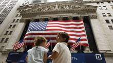 Two children sit on a bench outside the New York Stock Exchange August 9, 2011 (LUCAS JACKSON)