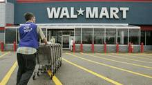 A Wal-Mart employee pushes a line of shopping carts toward the entrance of a Wal-Mart store, in Walpole, Mass., in this May 11, 2007 file photo. Growth in the U.S. service sector slowed in March. (Steven Senne/AP)
