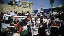 Palestinian women hold signs and photographs during a protest against the fighting in Gaza, at the Damascus gate in Jerusalem's old city, Thursday, July 24, 2014. (Mahmoud Illean/Associated Press)