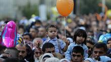 A boy holds a balloon after prayers during the Muslim holiday of Eid al-Fitr in Jerusalem's Old City on July 28, 2014. (AMMAR AWAD/REUTERS)