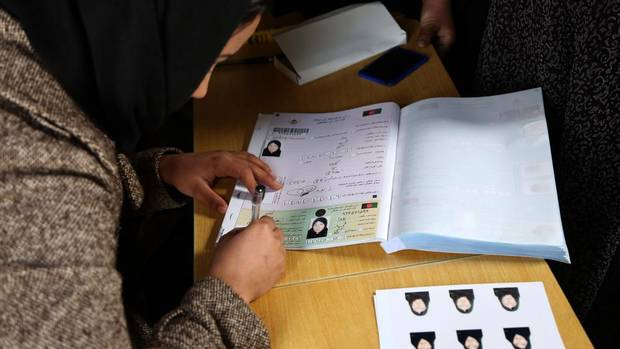 "An employee of the Afghan Independent Election Commission reviews a voter's documents at a women's voter registration center in Kabul, Afghanistan, Monday, March 17, 2014. Nine Afghan presidential candidates are campaigning in the presidential election slated for April 5, 2014. The Taliban have threatened to ""use all force"" to disrupt the election and warned voters to stay away from the polls. (Rahmat Gul/AP)"