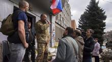 A pro-Russian activist, calling himself Vasily, second left, speaks to other protesters at barricades, with a Russian national flag in front of an entrance to the Ukrainian regional office of the Security Service in Luhansk, 30 kilometers west of the Russian border, in Ukraine, on Wednesday, April 9, 2014. (Igor Golovniov/Associated Press)